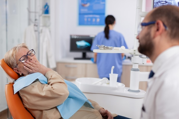 Elderly patient waiting diagnostic from dentist doctor sitting on dental clinic chair. senior woman in healthcare hospital accusing and complaining about tooth.