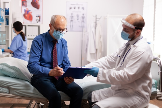 Пациент пожилого возраста в маске читает документы во время covid19