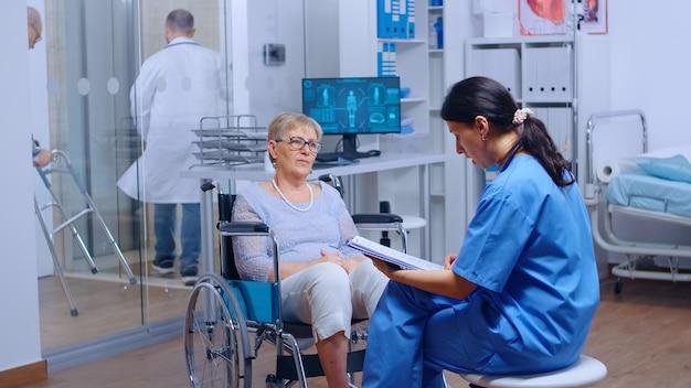 휠체어를 탄 보행 장애가 있는 노인 환자는 회복 클리닉이나 병원에서 의학적 조언을 구합니다. 고령자 장애 여성 의료 지원 의료 보험 마비 사람