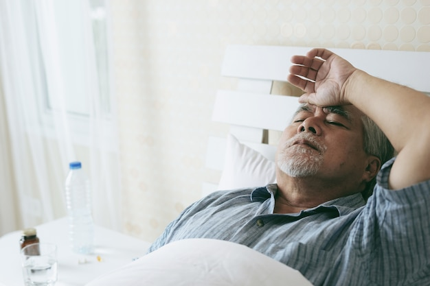 Elderly patients in bed, asian senior man patients headache medical and healthcare concept