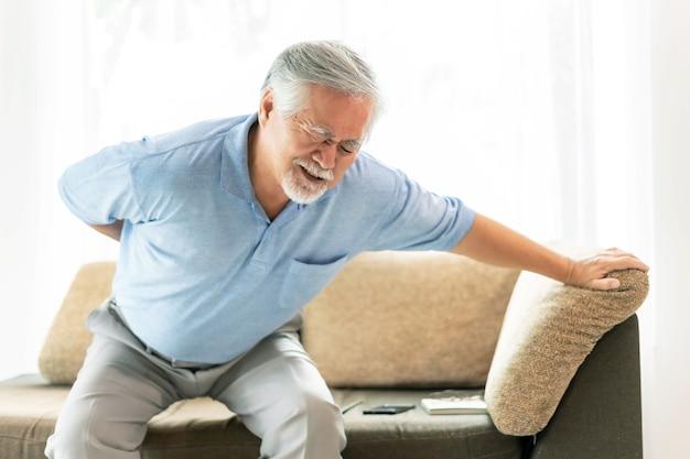 ソファの上の高齢患者、腰痛に苦しんでいるアジアの年配の男性-医療とヘルスケアの概念