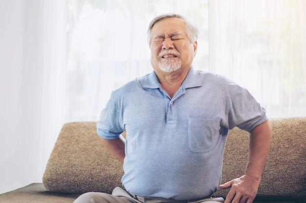 소파에 있는 노인 환자, 허리 통증으로 고통받는 아시아 노인 - 의료 및 건강 관리 개념