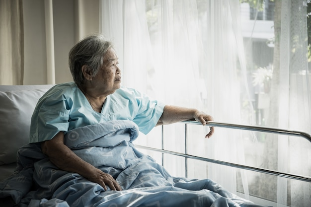 Elderly patients sitting in bed waiting for relatives to visit with loneliness.