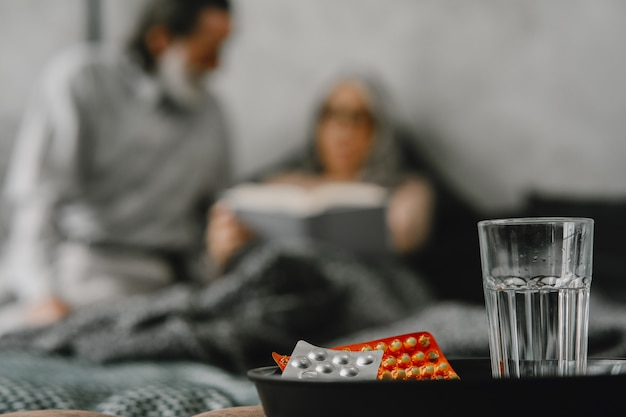 Elderly people focus on pills and glass of water on table.
