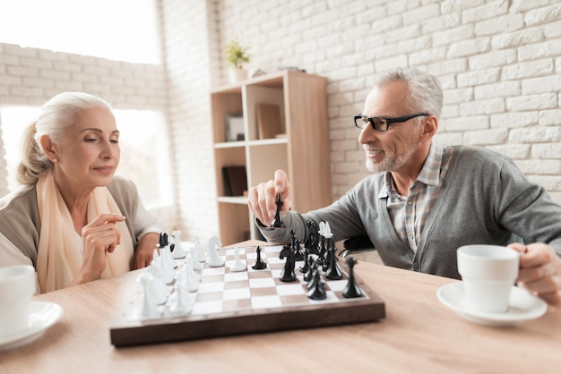 Elderly people play chess in nursing home.