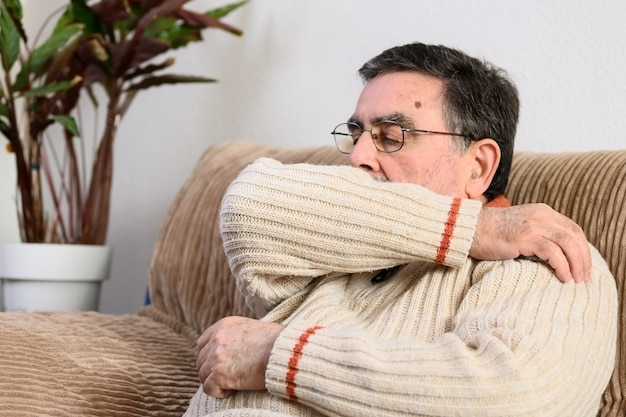 Elderly people sneezing, coughing into her sleeve or elbow to prevent spread covid-19.