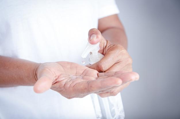Пожилые люди моют руки спиртом. предотвратить коронавирус