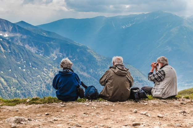 Elderly people with backpacks are sitting on the ground high in the mountains