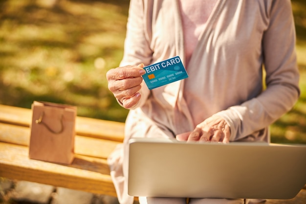 An elderly person holding a blue banking card in her right hand