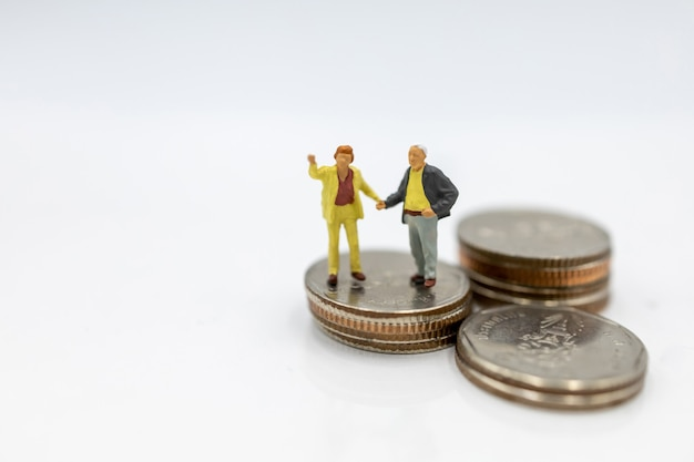 Elderly person standing on coins stack