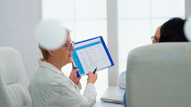高齢の医師は、病気の患者のリストを提示するクリップボードを指している医学的問題について話し合うためにブレインストーミングを行っています。病気の症状について話し合う病院のオフィスで働く医師のチーム