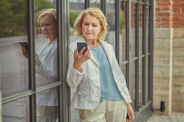 그녀의 손에 휴대 전화를 들고 약 62 세 노인 예쁜 비즈니스 여성이 심각한 얼굴로 메시지를 읽고 있습니다.