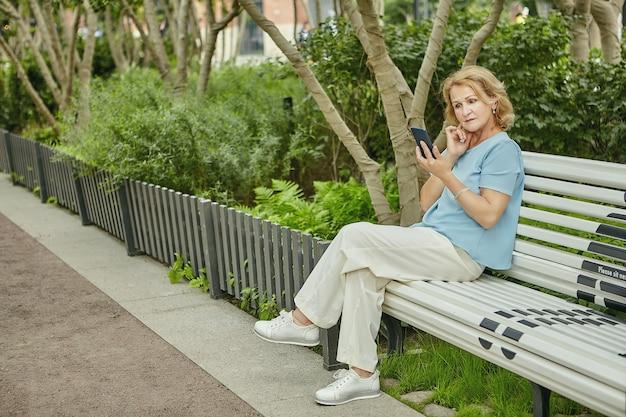 62 세 정도의 노인 예쁜 백인 여성이 공원 벤치에 앉아 핸드폰을보고 있습니다.