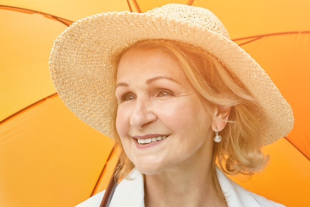 Elderly pretty woman about 60 years old in hat is smiling while standing under orange umbrella outdoor during day.