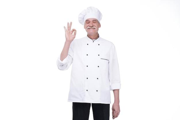 Пожилой профессиональный шеф-повар старший мужчина позирует с хорошо синглом, изолированным над белой стеной