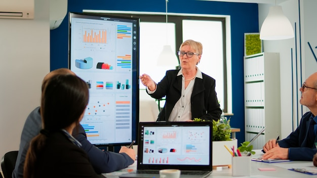 Elderly project manager pointing at desktop presenting statistical data, briefing diverse group of employees. multiethnical team working in professional startup financial company during conference