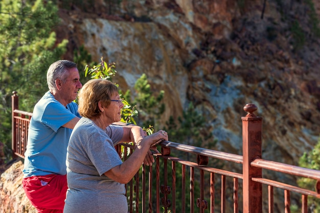 An elderly or retired couple leaning on railings looking out to mines