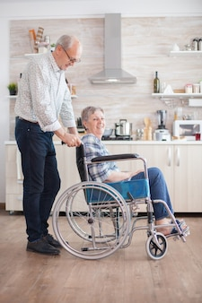 Elderly retired man helping his wife with walking disability. disabled senior woman sitting in wheelchair in kitchen looking through window. living with handicapped person. husband helping wife with d