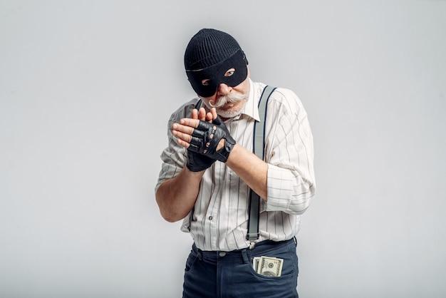 Пожилой грабитель в маске изолирован, гангстер. зрелый старший мужчина