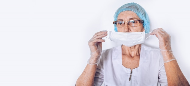 Elderly sad tired mature woman doctor or nurse in a white medical coat, gloves, puts on face mask wearing personal protective equipment isolated. healthcare and medicine concept. covid-19 pandemic