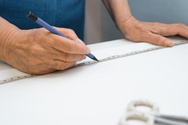 Пожилая швея разрабатывает одежду в помещении. крупный план руки старшей женщины зарисовки одежды на ткани. селективный акцент на пришивание ленты