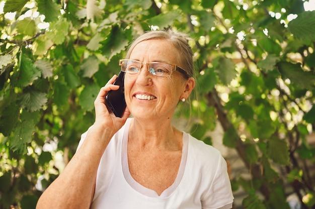 Elderly senior happy woman in prescription eyeglasses speaks smartphone outdoor