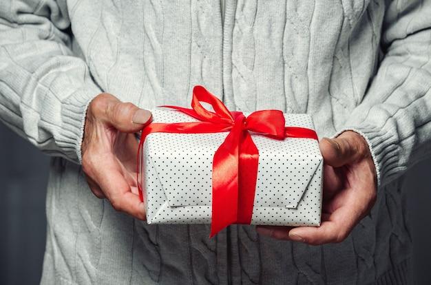 Пожилой старший держит рождественский подарок