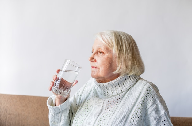 水のガラスを保持している高齢者シニア