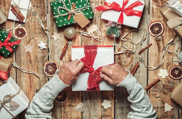 Руки пожилого человека, упаковывающие рождественские подарки на столе