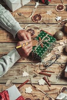 Руки пожилого человека подписывают рождественские подарки на столе