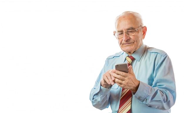 Пожилой старший человек используя его мобильный телефон изолированный на белой предпосылке.