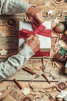 Пожилые старшие мужские руки упаковывают рождественские подарки