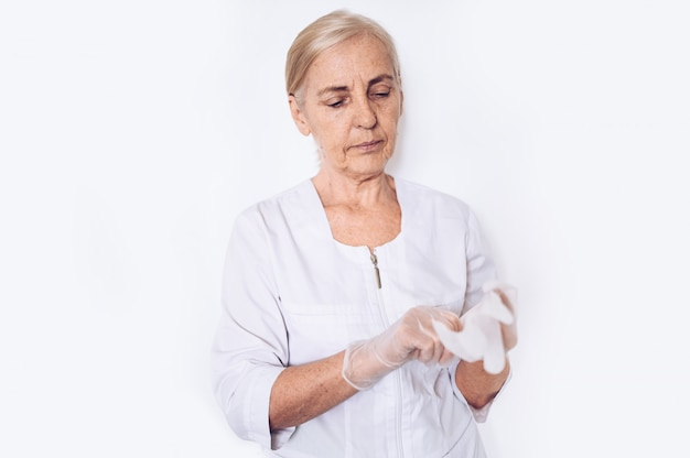 Elderly senior mature woman doctor or nurse in a white medical coat puts on gloves wearing personal protective equipment isolated. healthcare and medicine concept. covid-19 pandemic crisis