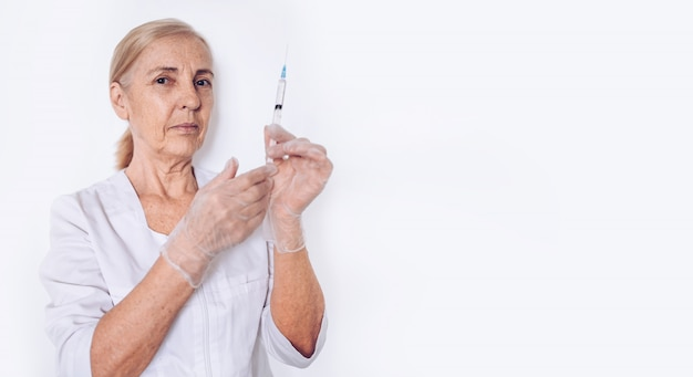 Elderly senior mature woman doctor or nurse with syringe in a white medical coat and gloves wearing personal protective equipment isolated. healthcare and medicine concept. covid-19 pandemic crisis