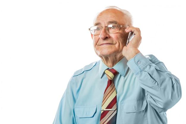 彼の携帯電話を使用して、白い背景で隔離の笑みを浮かべて高齢者上級老人。