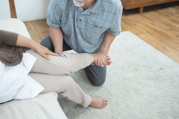 Elderly senior old grandmother fall down leg and ankle pain hurt,sit on couch with hand of grandfather support with treatment therapy at home.
