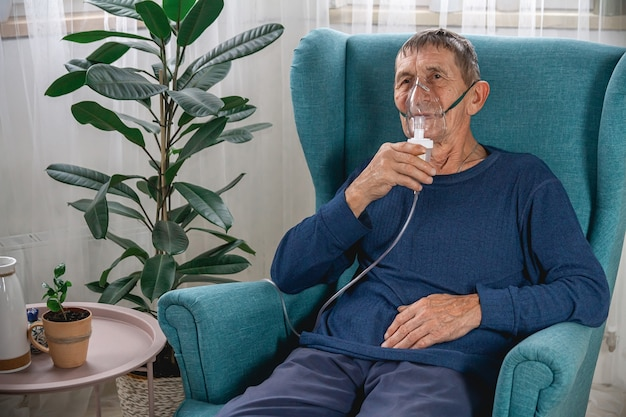 Elderly senior sits in a armchair with an oxygen mask in quarant