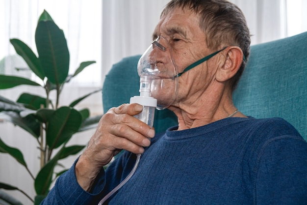 Elderly senior sits in a armchair with an oxygen mask in quarantine