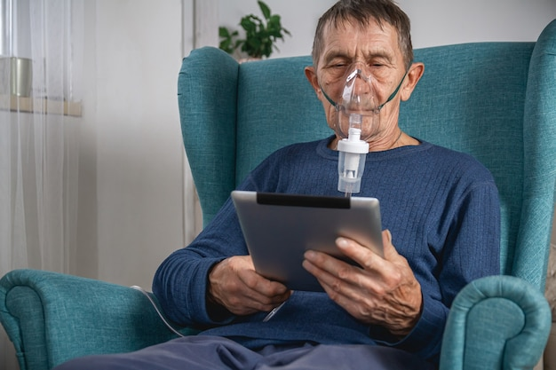 Elderly senior sits in a armchair with an oxygen mask and tablet
