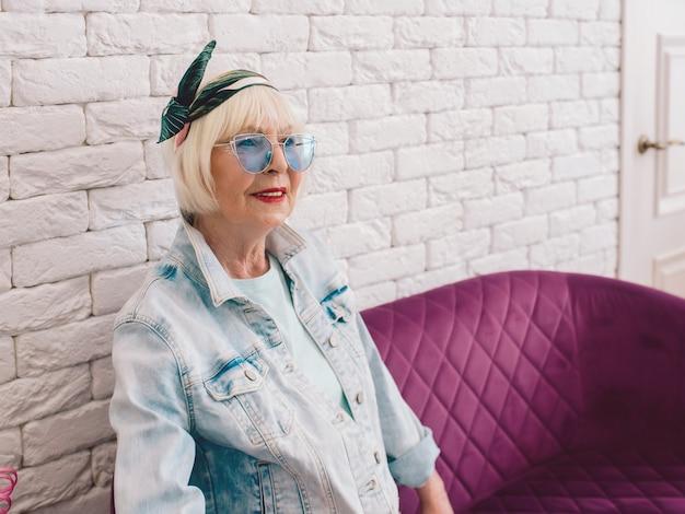 Пожилая старшая стильная женщина в синих солнцезащитных очках и джинсовой куртке сидит на диване в интерьере лофта