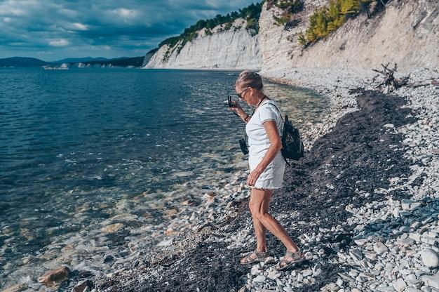Пожилые пожилые люди, путешествующие с рюкзаком, зрелая женщина, турист, гуляющий с фотографиями на побережье