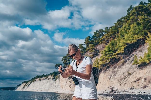 海岸で写真を撮って歩く高齢者シニア旅行バックパッカー成熟した女性観光客