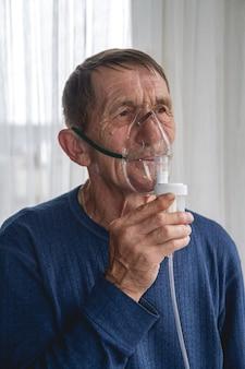 酸素マスクを持った高齢者