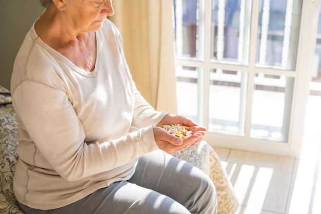 自宅のベッドに座って色とりどりの錠剤、丸薬、カプセルをカップ状の手で見ている年配の女性、薬を服用しながら考えている女性。手にたくさんの薬を持っている女性