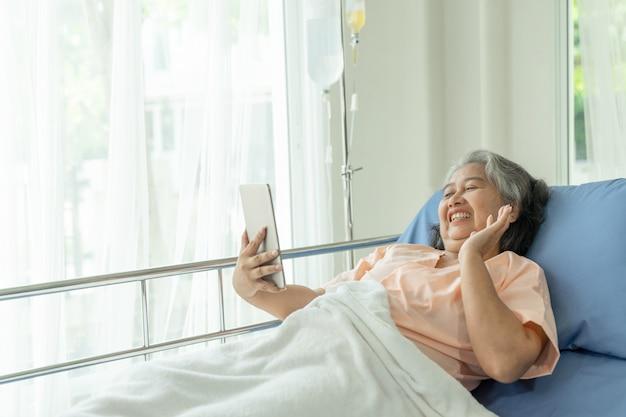 子孫の親戚にスマートフォンを使用して病院のベッドの患者の高齢の年配の女性患者は幸せ-シニア女性の医療とヘルスケアの概念を感じる