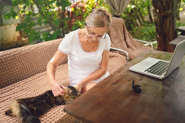 Пожилая женщина с домашней кошкой использует беспроводные наушники, работая онлайн с портативным компьютером