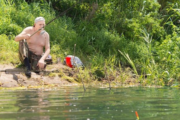 Elderly shirtless man fishing on a lake