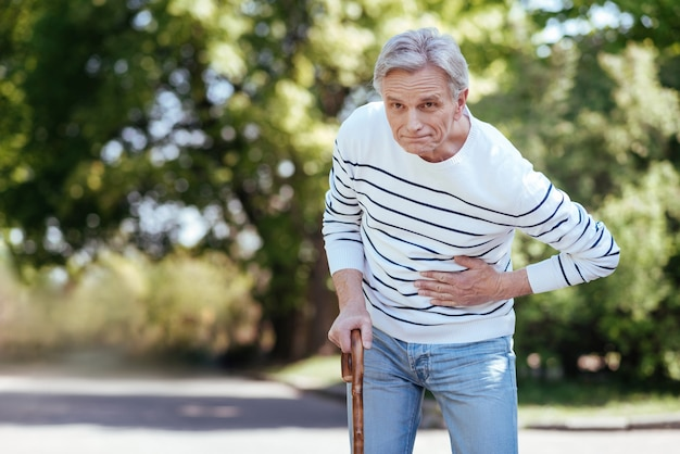 Elderly shocked ill man touching his chest and feeling bad while suffering from stomachache outdoors
