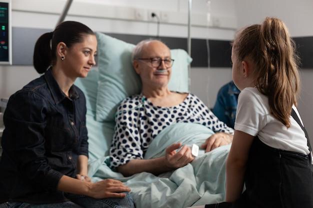 思いやりのある孫娘と話しているベッドで休んでいる年配の病気の老人
