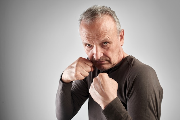 Elderly stylish man in boxing pose with strong face holds blow of fate